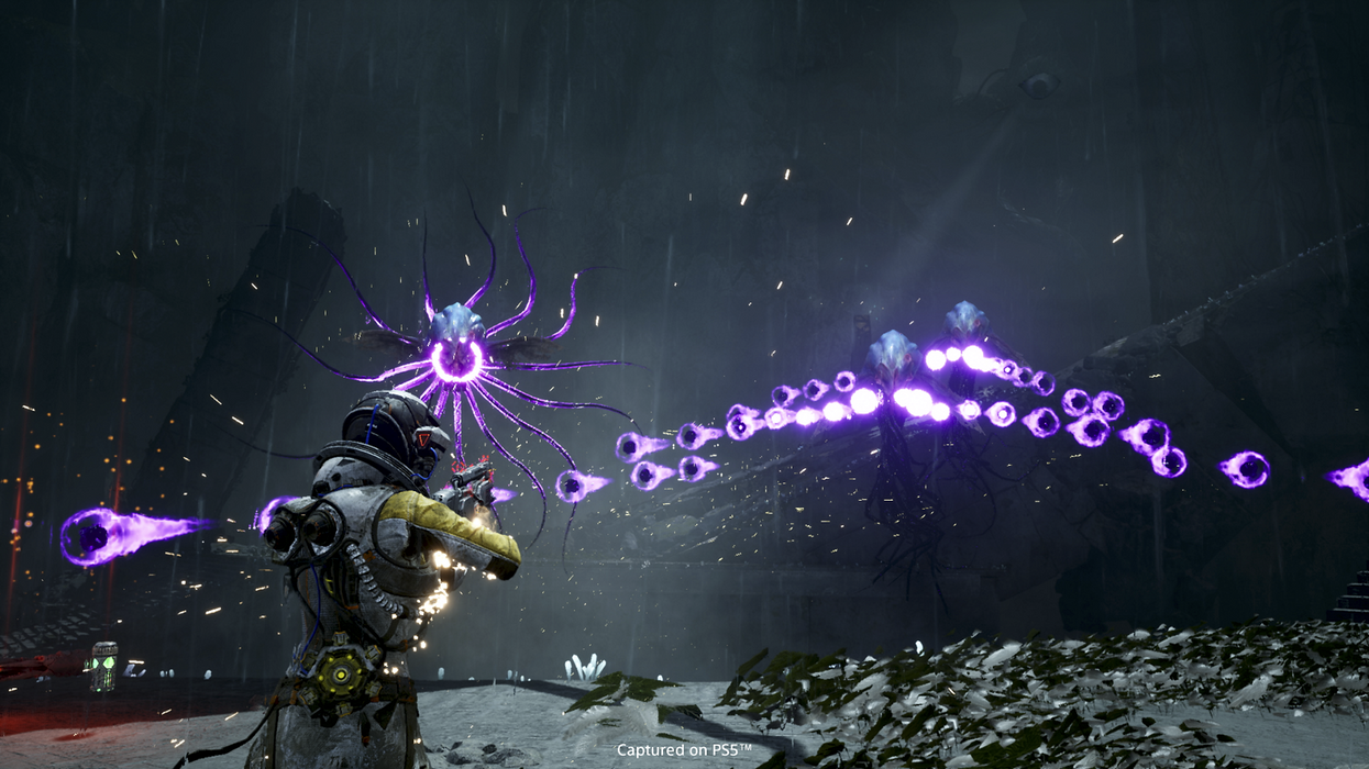 The main character of roguelike shooter Returnal engaging in combat.