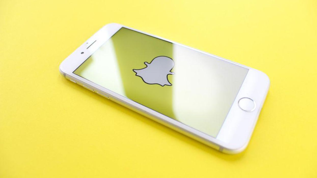 The Snapchat ghost logo on a white iPhone and a yellow background.