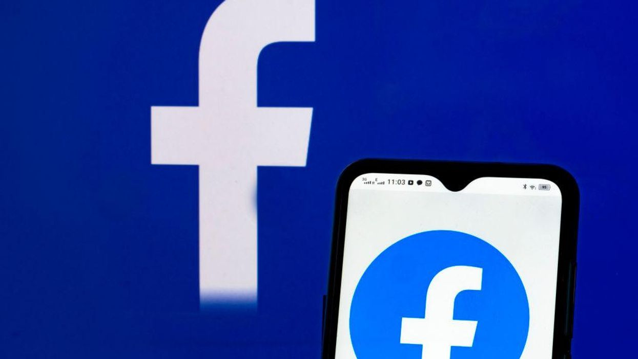 The facebook logo displayed on a smartphone screen, in front of a backdrop of the Facebook logo.