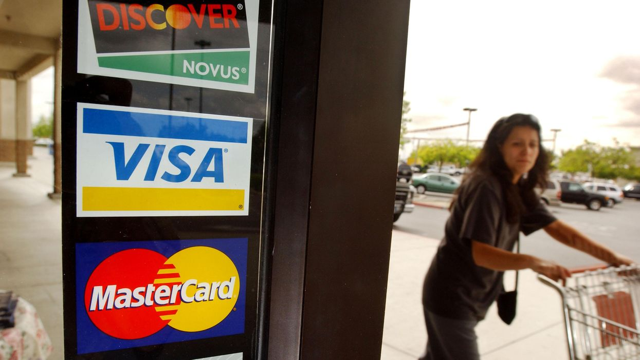 The Visa and Mastercard logos displayed on the door of a retail store