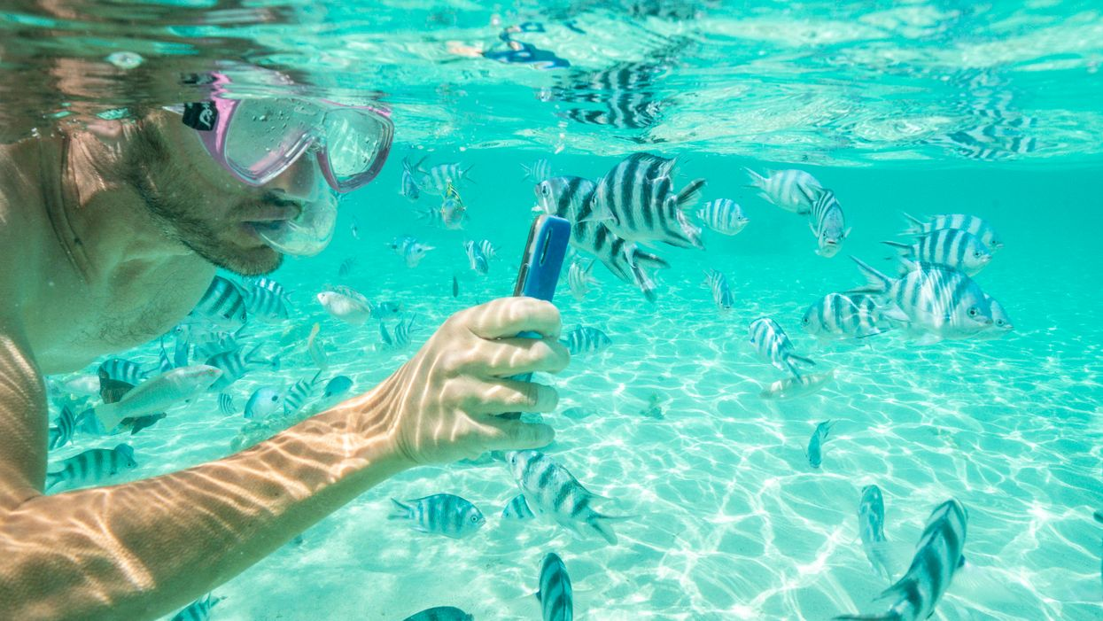 A man snorkeling with an iPhone.