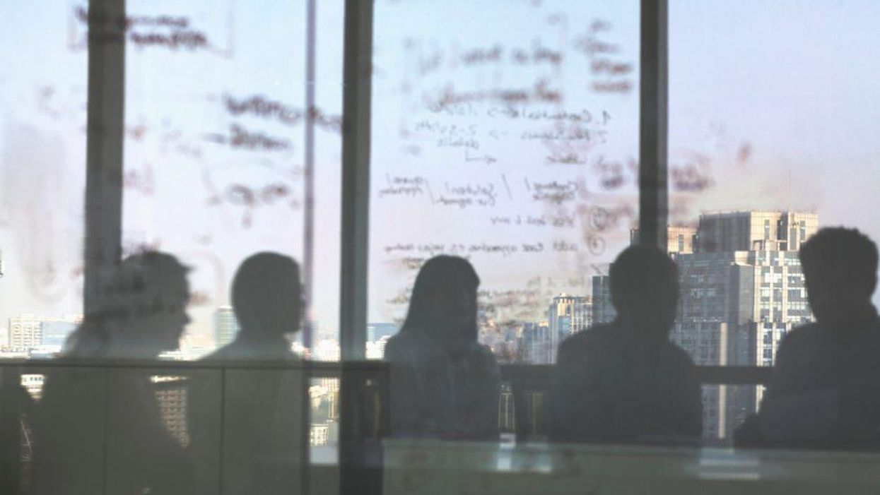 People in an office seen through a window