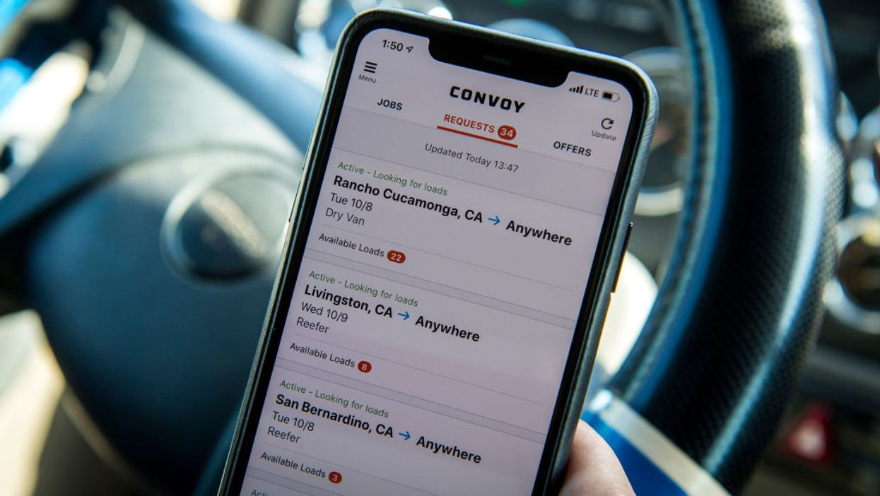 Trucker holds phone with Convoy app