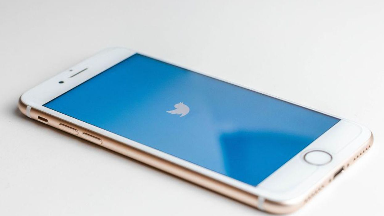 An iPhone with the Twitter logo on the screen.