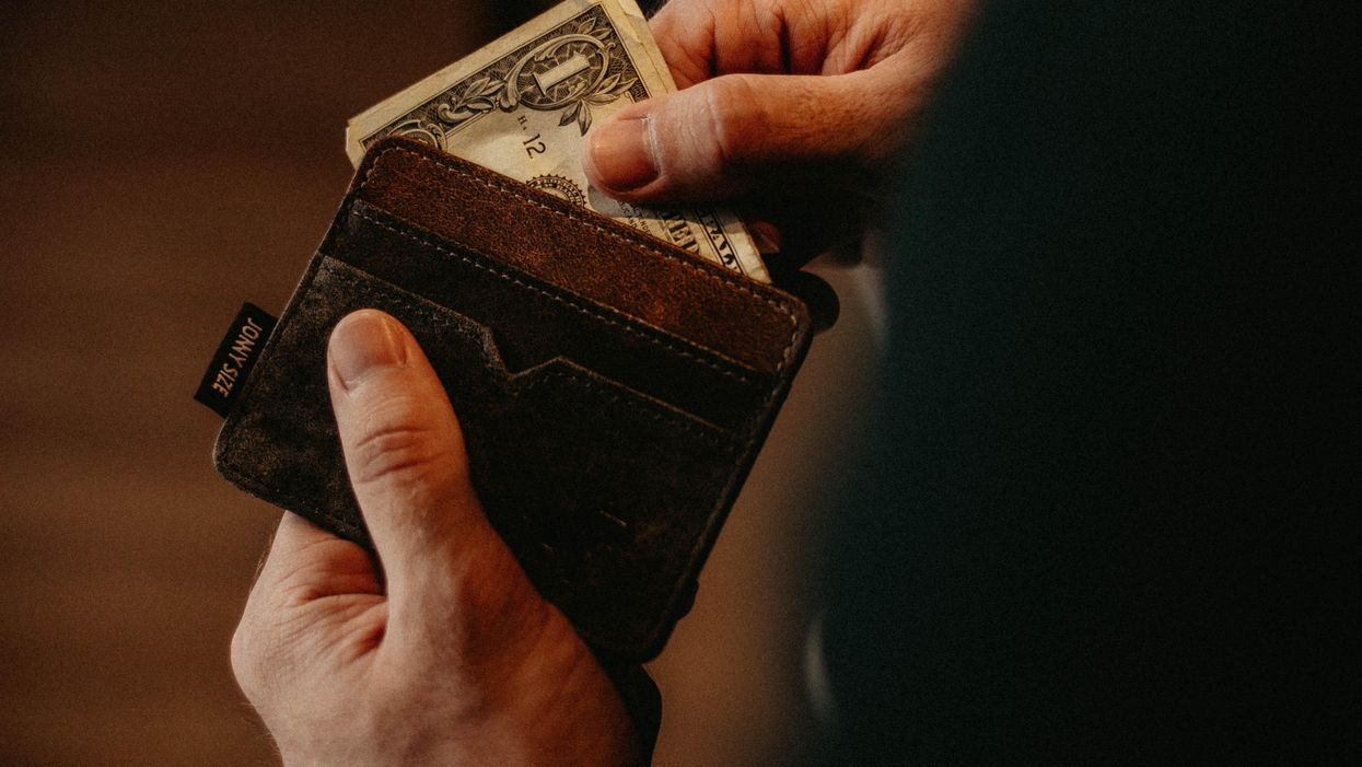 A person pulls cash out of a wallet.