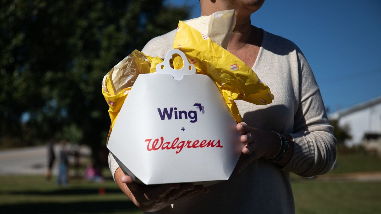 A customer opens a package delivered by a Wing Aviation LLC drone